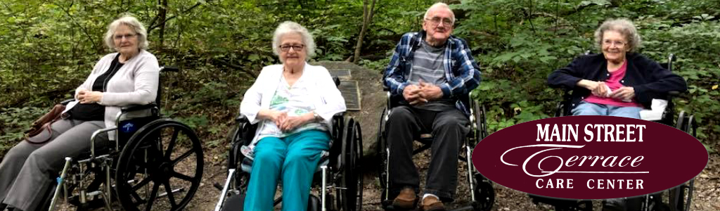 four residents in wheelchair outside on wooded park walk